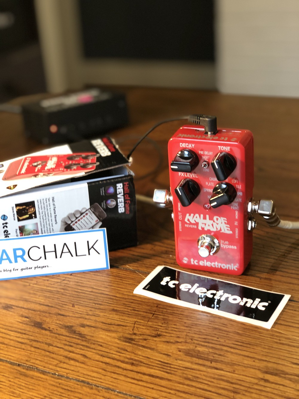 Angled shot of the TC Electronic Hall of Fame reverb pedal with boxes, stickers, and power supply in a blurred background