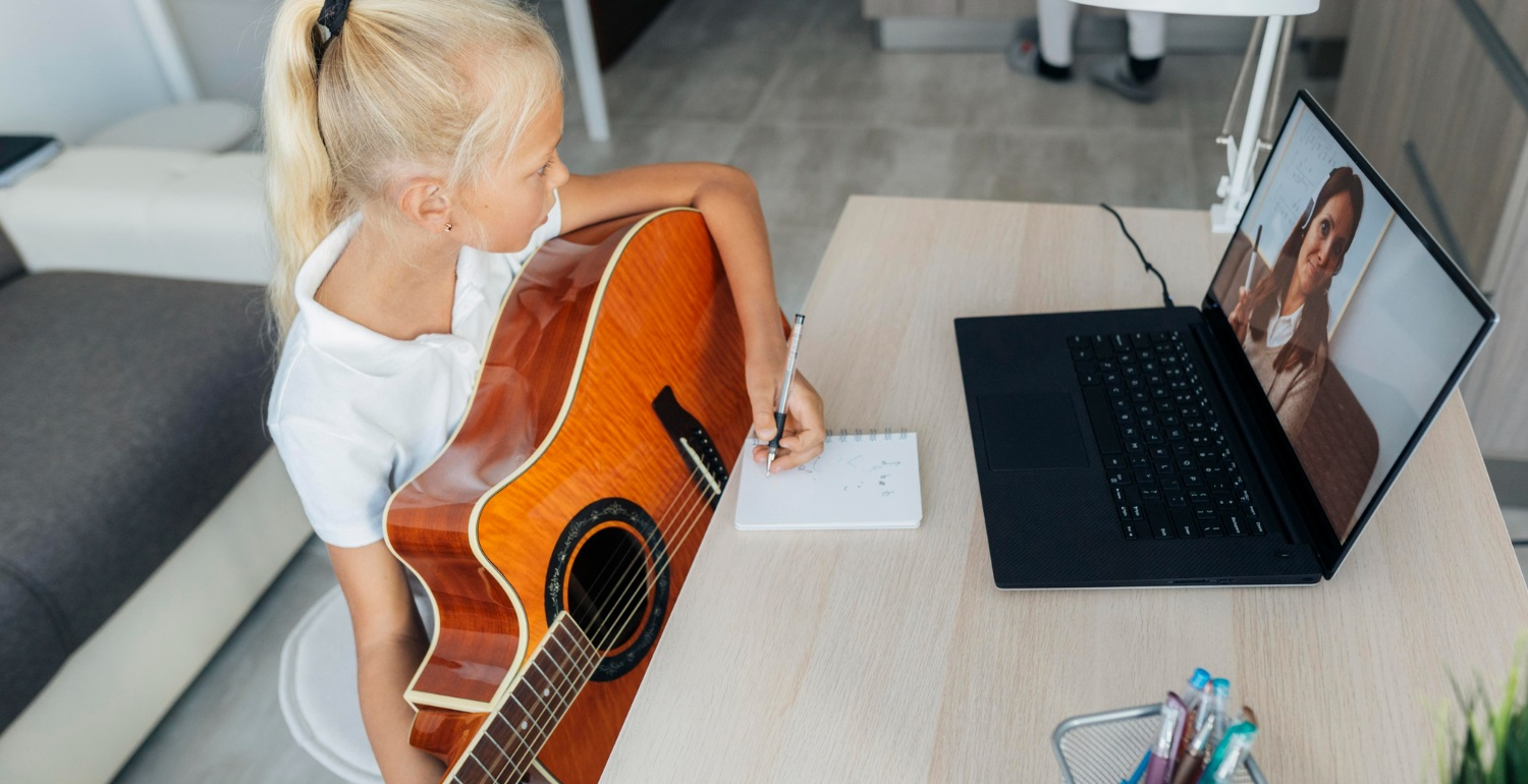 Young girl taking guitar lessons from an online video